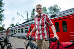 Tourist with bikes and luggage on suburban railway platform wait Stock Photos