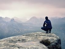 Tourist in black  sit on cliff& x27;s edge looking to misty hilly valley Stock Photography