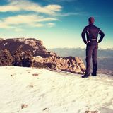 Tourist in black is standing on snowy view point. National park Alps park in Italy. Sunny winter morning. Royalty Free Stock Images