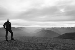 Tourist in black with white cap is standing above Alpine valey.. National park Alps park in Italy. Royalty Free Stock Photos