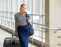 Tourist blonde girl in a striped blouse standing on the station with a large suitcase and passport with tickets Stock Photos
