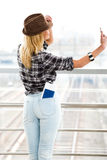 Tourist blonde girl in a striped sweater and a hat standing with a train station and makes selfie. Back view Royalty Free Stock Photo