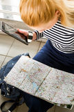 A tourist blonde woman in striped sweater sitting with a tablet and is looking at the map. View from above Stock Photos