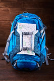 Tourist blue big backpack and map against wooden background. Royalty Free Stock Photography