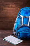 Tourist blue big backpack and map against wooden background. Stock Photography