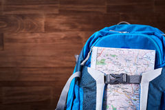 Tourist blue big backpack and map against wooden background. Stock Photo