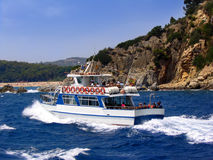 Tourist boat. A tourist boat near a cliff and a beach (Costa Brava, Spain Stock Image