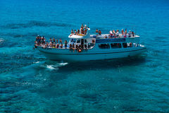 Tourist boat approaching the sea caves of Ayia Napa Royalty Free Stock Image
