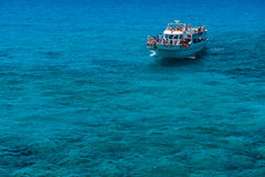 Tourist boat approaching the sea caves of Ayia Napa Royalty Free Stock Photography