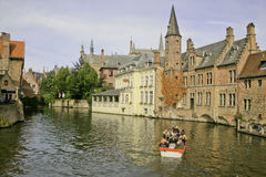 A Tourist Boat on the Canal, Bruges, Belguim. A boat full of sightseeing tourists floating down the canal in Bruges, Belgium. Classic buildings line the canal Stock Photo