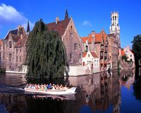 Tourist boat on canal, Bruges. Stock Images