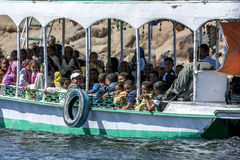A tourist boat crammed full of people travels along the River Nile in the Aswan region of Egypt. A boat crammed full of tourists travels along the River Nile in Stock Photo