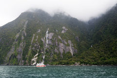 Tourist boat cruises in the fjord of Milford Sound, South island of New Zealand Stock Photography