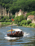 Tourist boat on the Dordogne River, France. Boat cruising down the Dordogne past La Roque Gageac, France royalty free stock photo