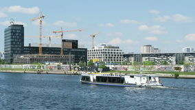 Tourist boat driving on spree river along the concert hall and in background TV Tower of Berlin. stock footage