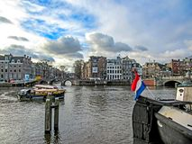 Tourist boat and Dutch flag on city canal in Amsterdam, Holland, Netherlands. Amsterdam, Holland, Netherlands – January, 2019: Tourist boat and Dutch flag stock photos