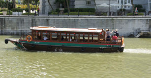 Tourist boat exploring Singapore from riverside Royalty Free Stock Images