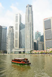 Tourist boat floating on Singapore river Royalty Free Stock Photos
