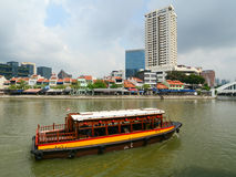 Tourist boat floating on Singapore river Royalty Free Stock Images