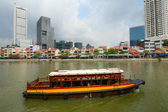 Tourist boat floating on Singapore river Stock Images