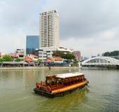 Tourist boat floating on Singapore river Stock Photo