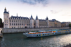 Tourist boat floats past the old castle in the evening on the Se Royalty Free Stock Photos