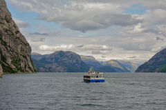 Tourist boat navigating a fjord. Tourist boat navigating a fjor in norway Royalty Free Stock Photo