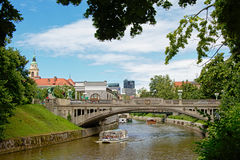 Tourist boat navigating under a bridge on Ljubljanica river. With historical and modern buildings in the background Royalty Free Stock Photos