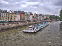 Tourist boat operated by Bateaux-Mouches with tourists onboard looking at the scenery, on the Seine River in Paris, France. Stock Photos
