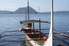 Tourist Boat Parked at Lake shore that cater to inter island travelers. In front of volcano stock photography