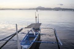 Tourist Boat Parked at Lake shore that cater to inter island travelers. In front of volcano stock image