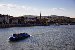 A tourist boat rides on the Danube River in Budapest, Hungary. The sun sets on a tourist boat riding on the Danube River in Budapest, Hungary stock photo