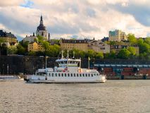 Tourist boat sailing on the lake on the background of beautiful buildings of Stockholm stock photo