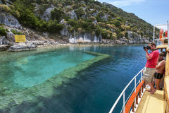 A tourist boat sales past a section of the Sunken City off Kekova Island in the western Mediterranean region of Turkey. Originally part of the ancient city of Royalty Free Stock Photos