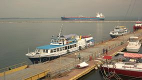 Tourist boat and tanker. Scales of business stock footage