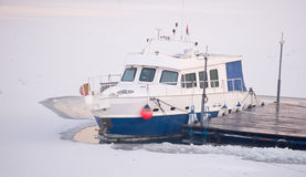 Tourist boat tied to the wooden dock on frozen river during cold Stock Photo