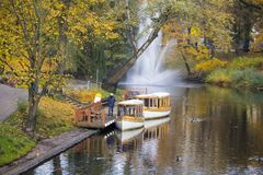 Tourist boats Autumn park in the center of Riga with fountain , Latvia Canal that flows through Bastion park autumn stock image