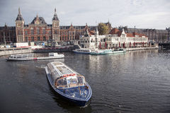 Tourist boats in front of central station amsterdam Stock Photography