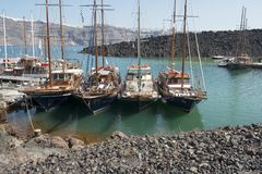 Tourist boats at Nea Kameni. Day trip tourist boats moored at Nea Kameni, the volcanic island in the caldera at Santorini, Greek Islands Stock Photography