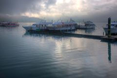 Tourist boats parking on peaceful water and moored to the floating docks of Shuishe Pier at Sun-Moon Lake. On a foggy morning in Nantou, Taiwan, with mountains royalty free stock image