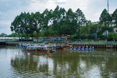 Tourist boats parking at wharf at downtown of Saigon. Ho Chi Minh, Vietnam - June 11, 2016: Tourist boats moving on the Nhieu Loc canal at Saigon. The tour is Royalty Free Stock Photo