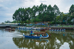 Tourist boats parking at wharf at downtown of Saigon. Ho Chi Minh, Vietnam - June 11, 2016: Tourist boats moving on the Nhieu Loc canal at Saigon. The tour is Stock Photos