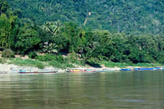 Tourist boats on shore of Mekong river Stock Photos