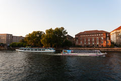 Tourist boats in Spree river Berlin Germany. Two touristic boats passing each other on the Spree river in East Berlin, Germany Royalty Free Stock Photos