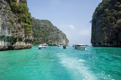 Tourist boats with tourists swim among the islands. PHI-PHI ISLAND, THAILAND - JANUARY 4: Tourists sail from the island to the island by boat, as part of an Stock Images