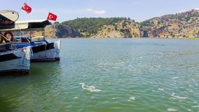 Tourist boats with the Turkish flag are moored on the bank of the Dalyan River. Habitat of the turtle Caretta caretta. Tourists sketched crabs in the water to stock video