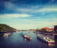 Tourist boats on Vltava river in Prague. Vintage retro hipster style travel image of turist boats on Vltava river in Prague, Czech Republic with grunge texture Stock Images