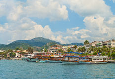 Tourist boats at waterfront promenade on summer day Stock Photos