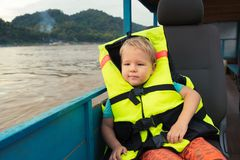 Tourist boy enjoy boat trip. Laos. Child wearing oversized life vest enjoy boat trip. Vang Vieng. Laos Stock Image