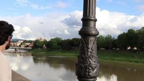 Tourist boy near Arno in Florence stock video footage